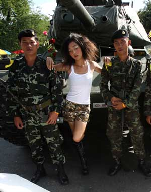 A Thai fashion college student conducts a photo shoot with soldiers keeping guard near the Government House in Bangkok